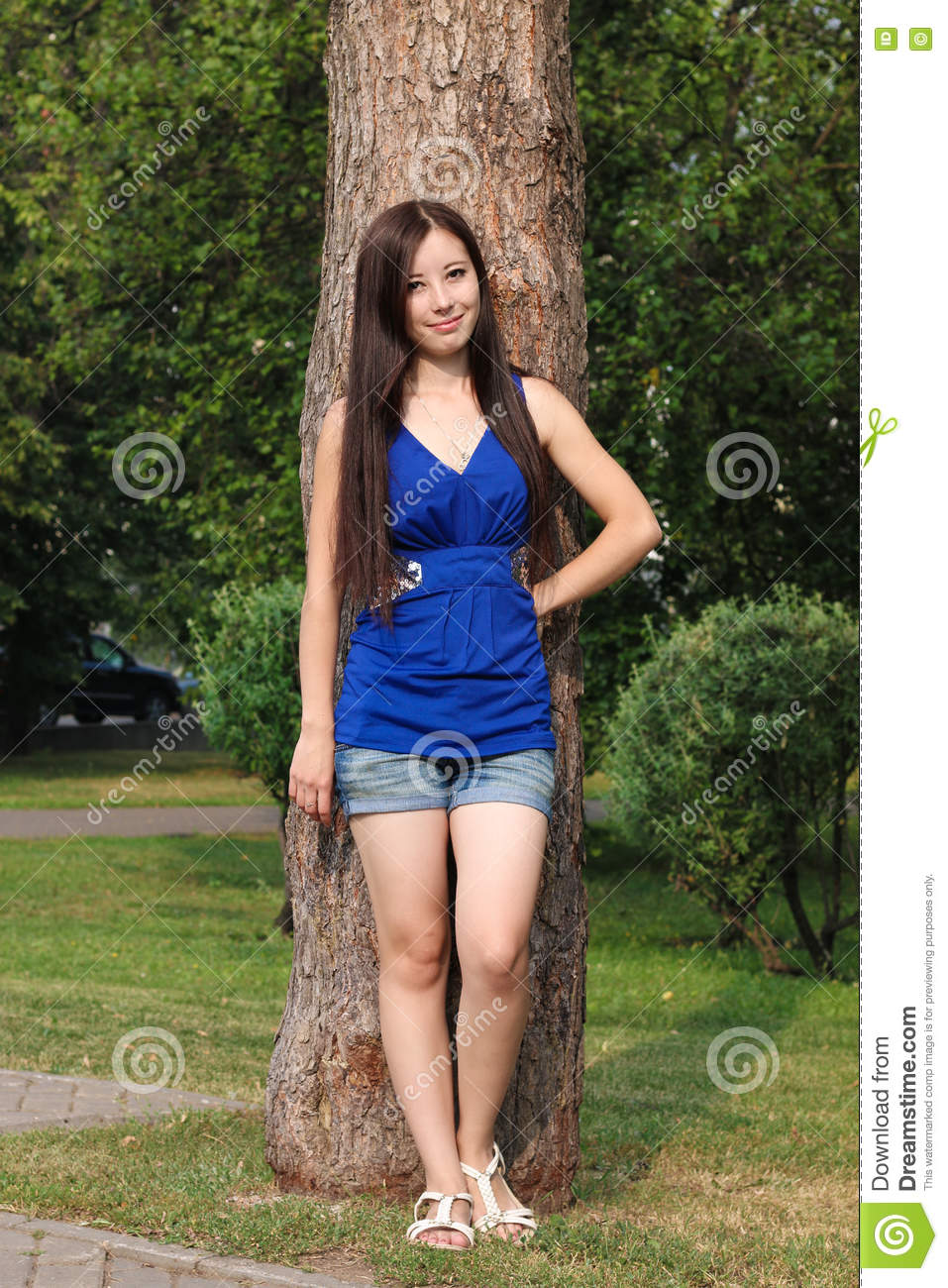 Young girl in shorts leaned against a tree in the Park