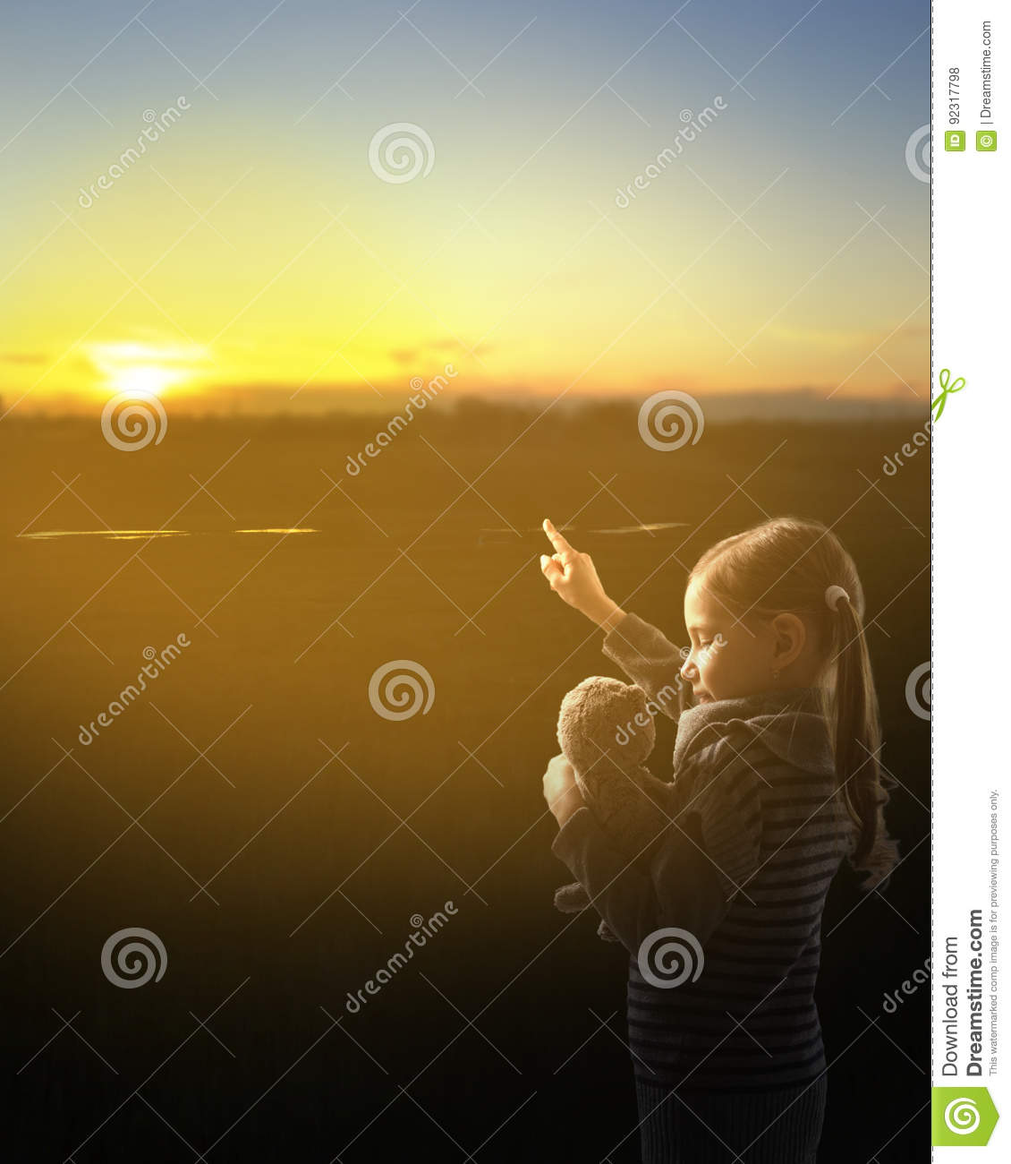 The young girl shows the plush toy at sunset.