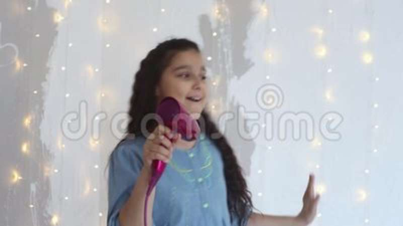 Young girl sings songs in a hair dryer and dances having a good mood  HD