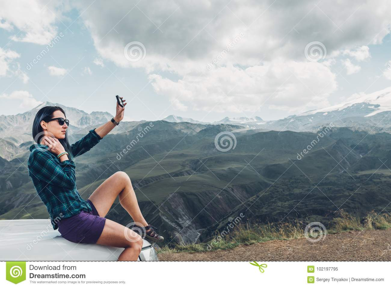 Young Girl Sits On Car And Makes Selfie On Smatrphone On Summer Mountain Background. Travel Discovery Journey Concept