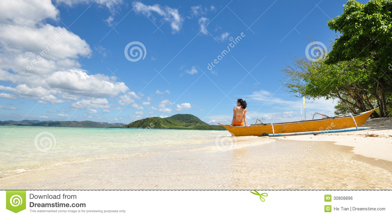 young bikini girl sits on the tip of a banca (a type of outrigger boat ...
