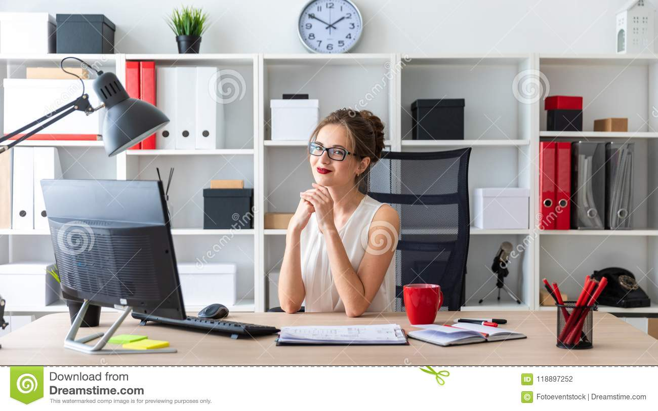 A young girl is sitting at the desk in the office.