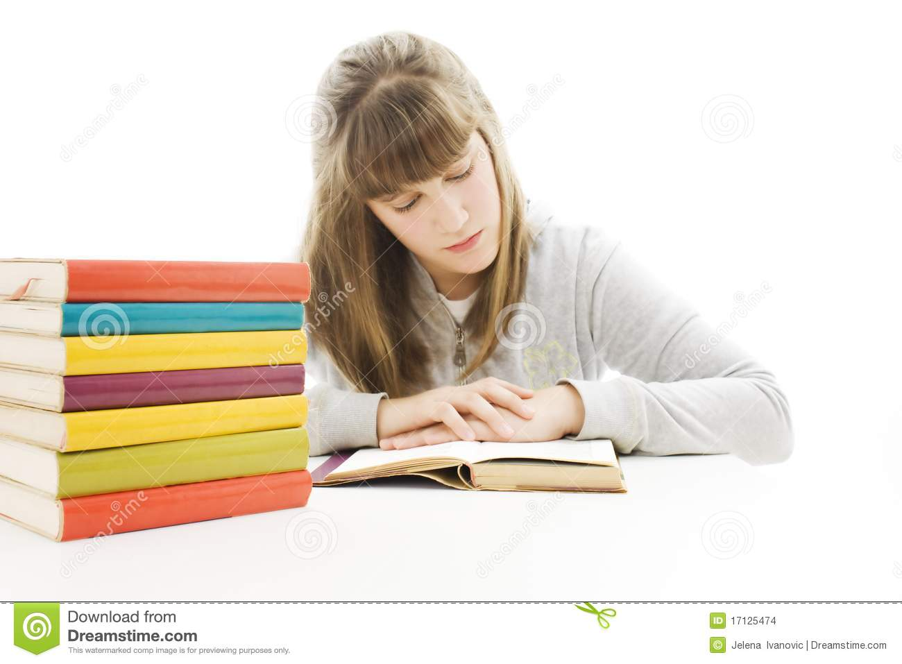 Young Girl Sitting At The Desk And Reading Book. Stock Images - Image ...