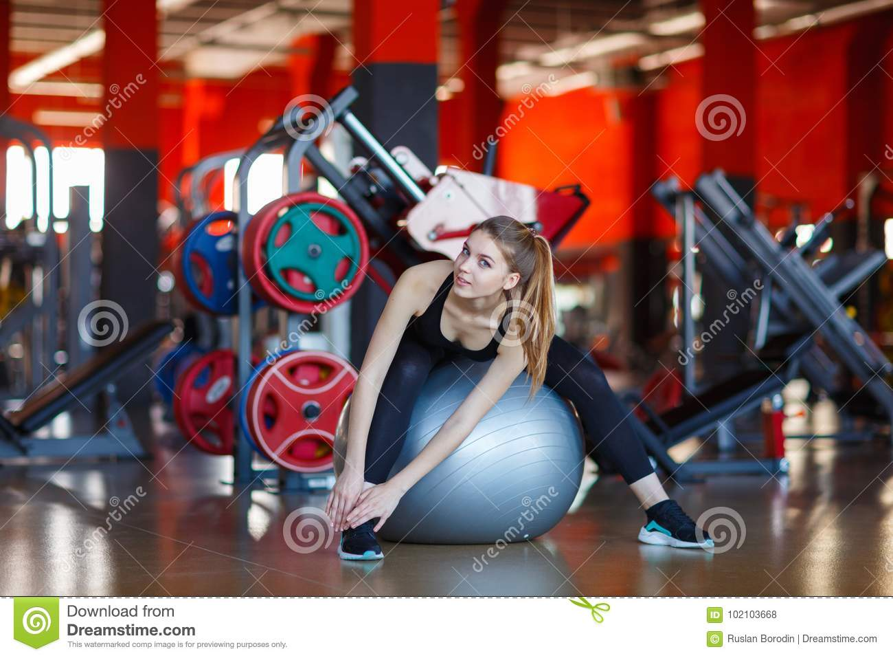 Young girl sitting on fitness ball in modern hall.