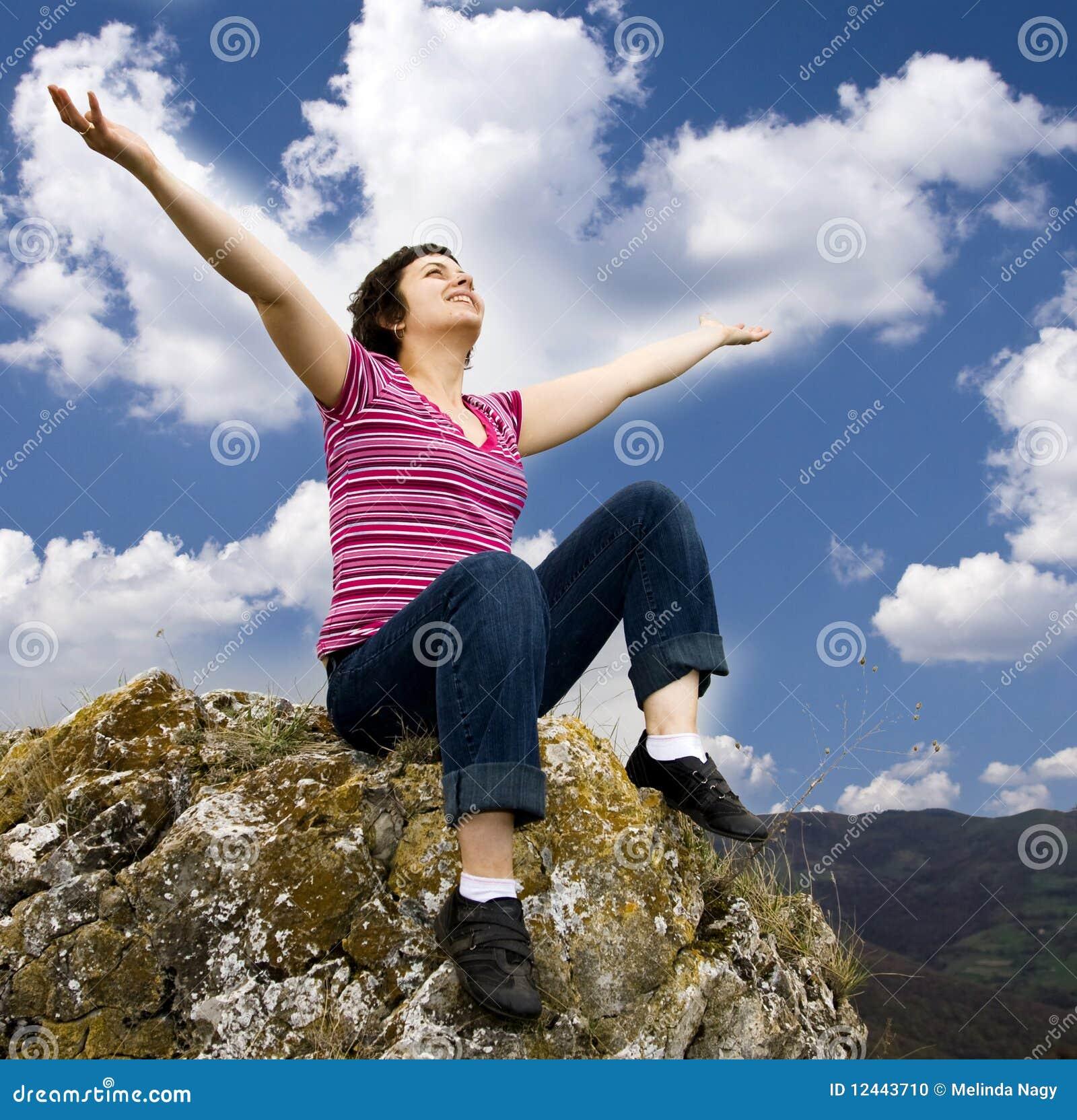 Girl sitting on rock congratulate