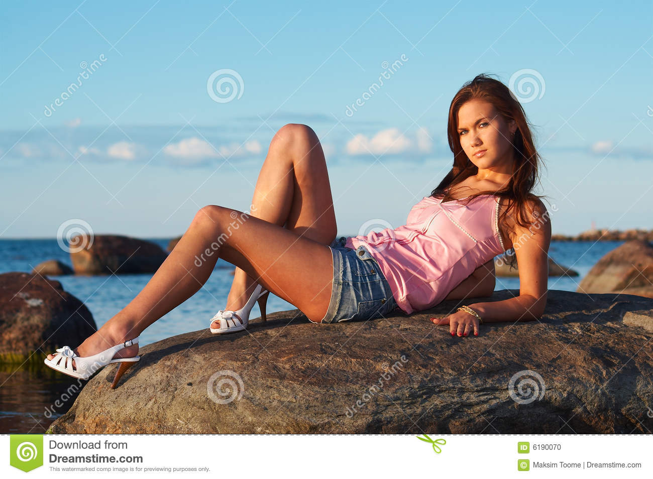 Young girl sitting on a stone