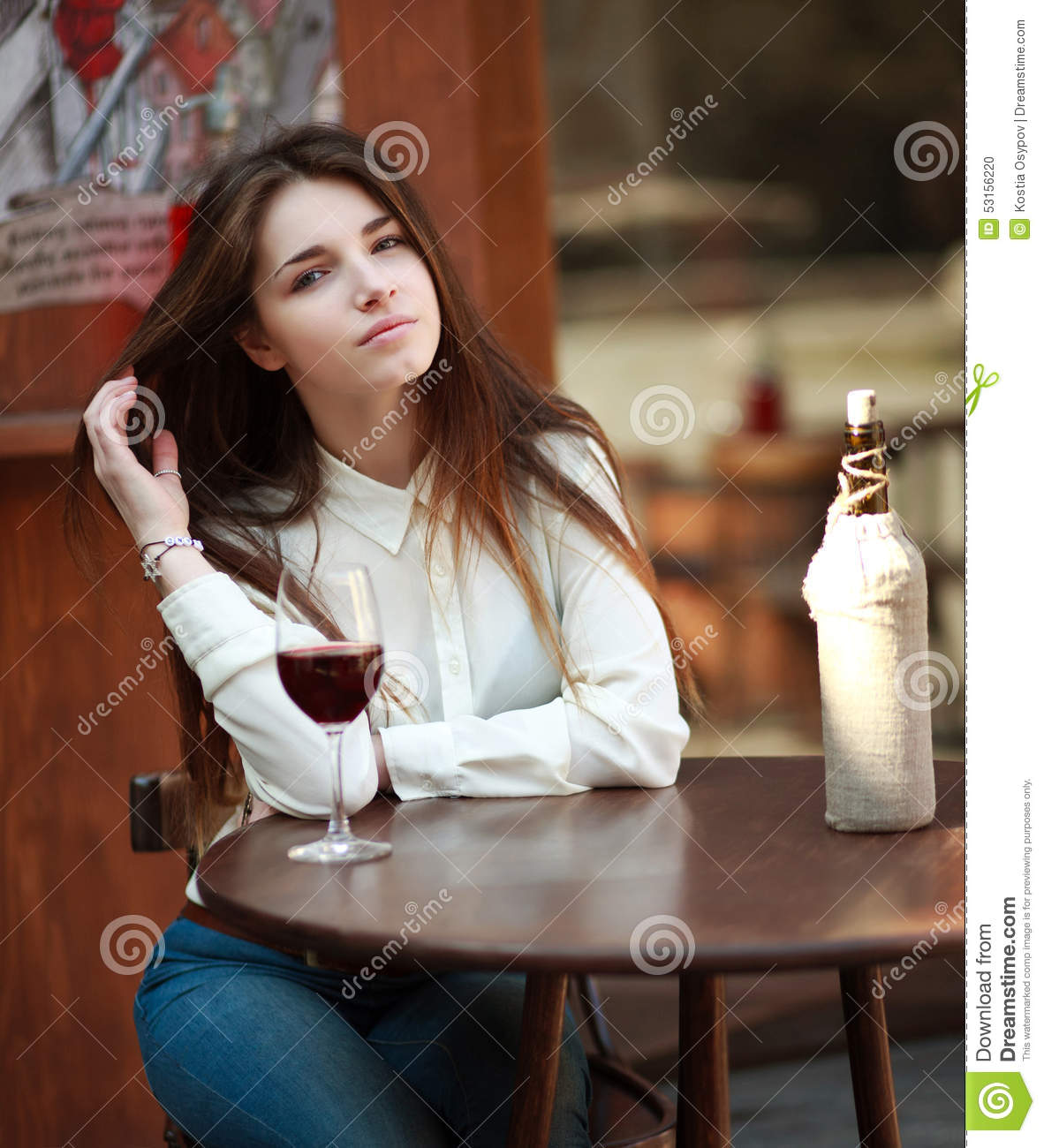 Young girl sitting at table in summer cafe with glass of wine