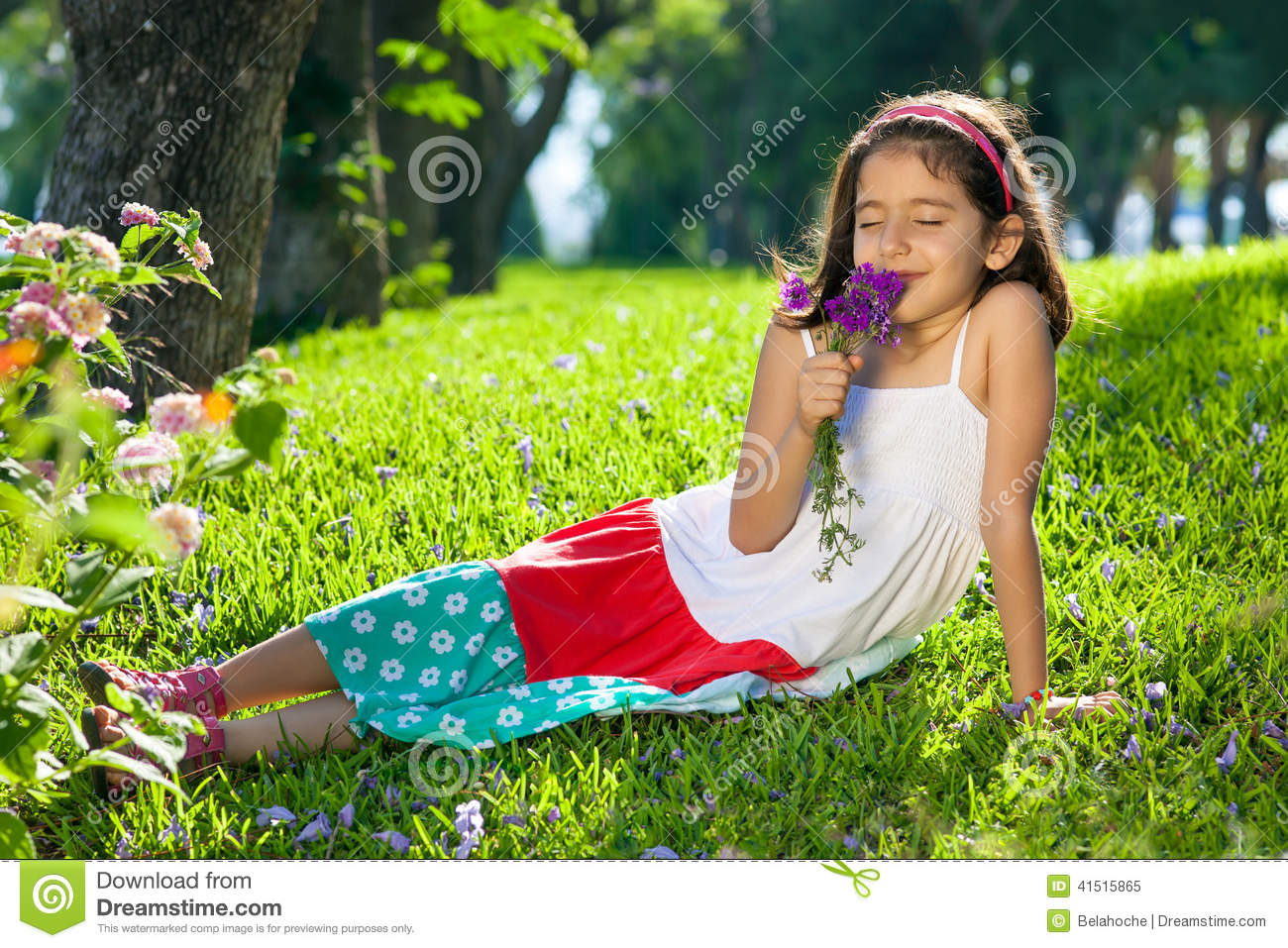 Young Girl Smelling Flowers in Her Hands.