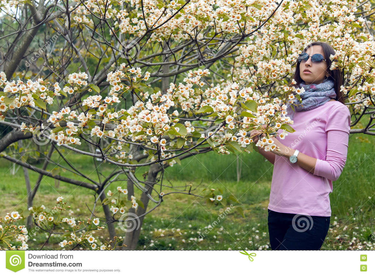 Young girl smelling little white flowers tree