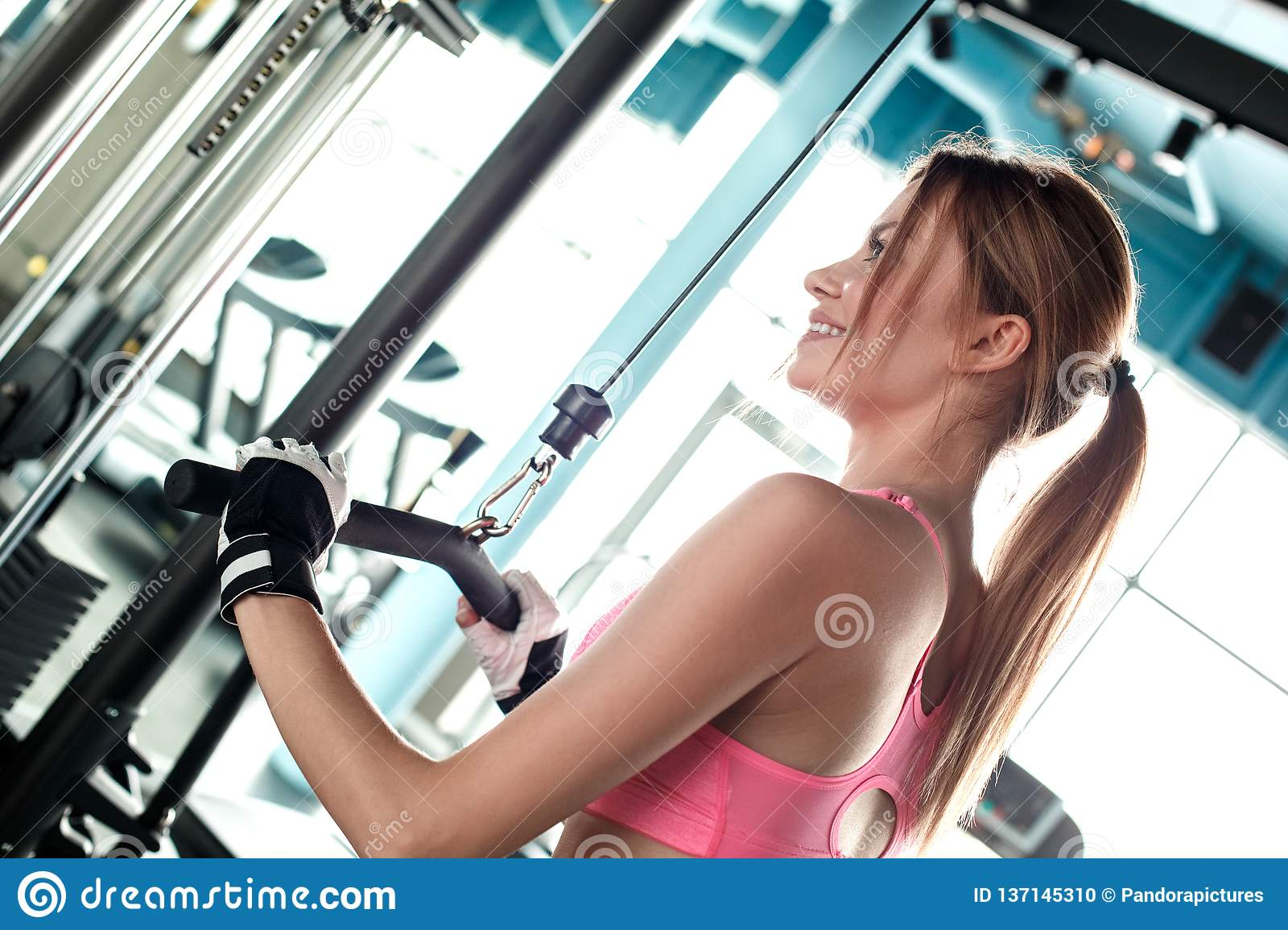 Young girl in sport gloves in gym healthy lifestyle exercising on cable machine holding bar looking aside cheerful back