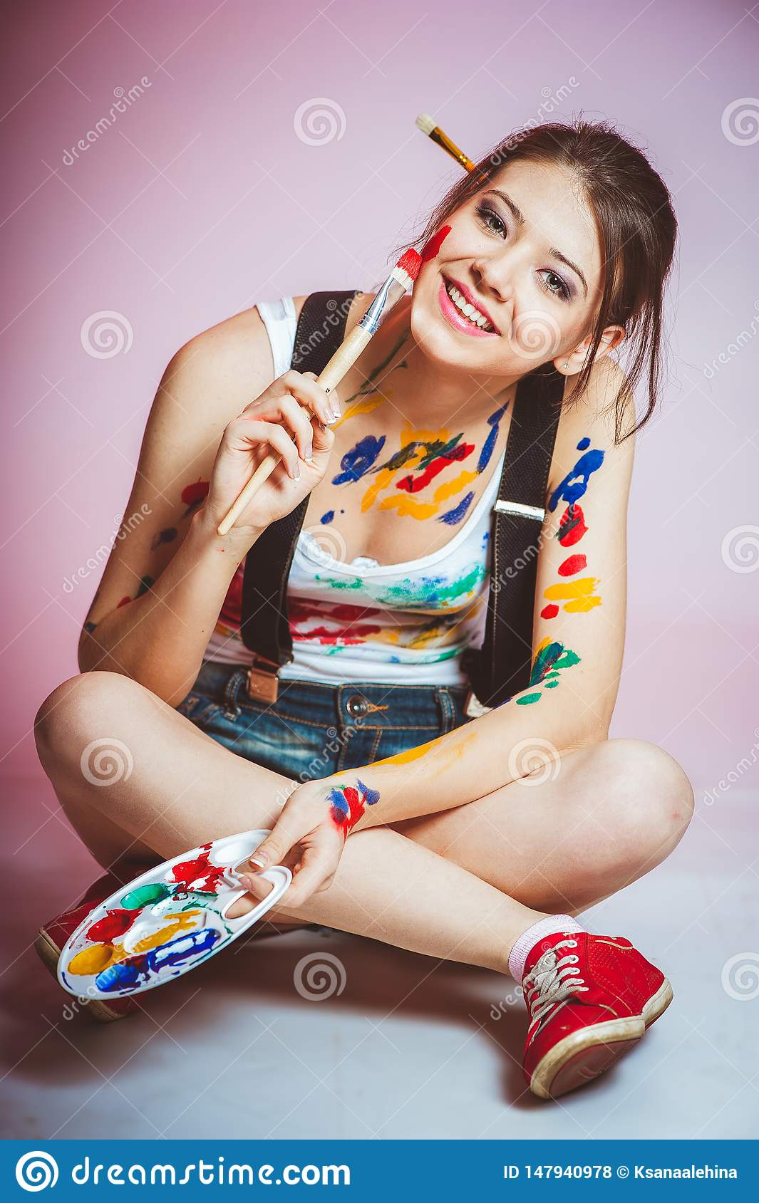 A young girl is stained with paint.