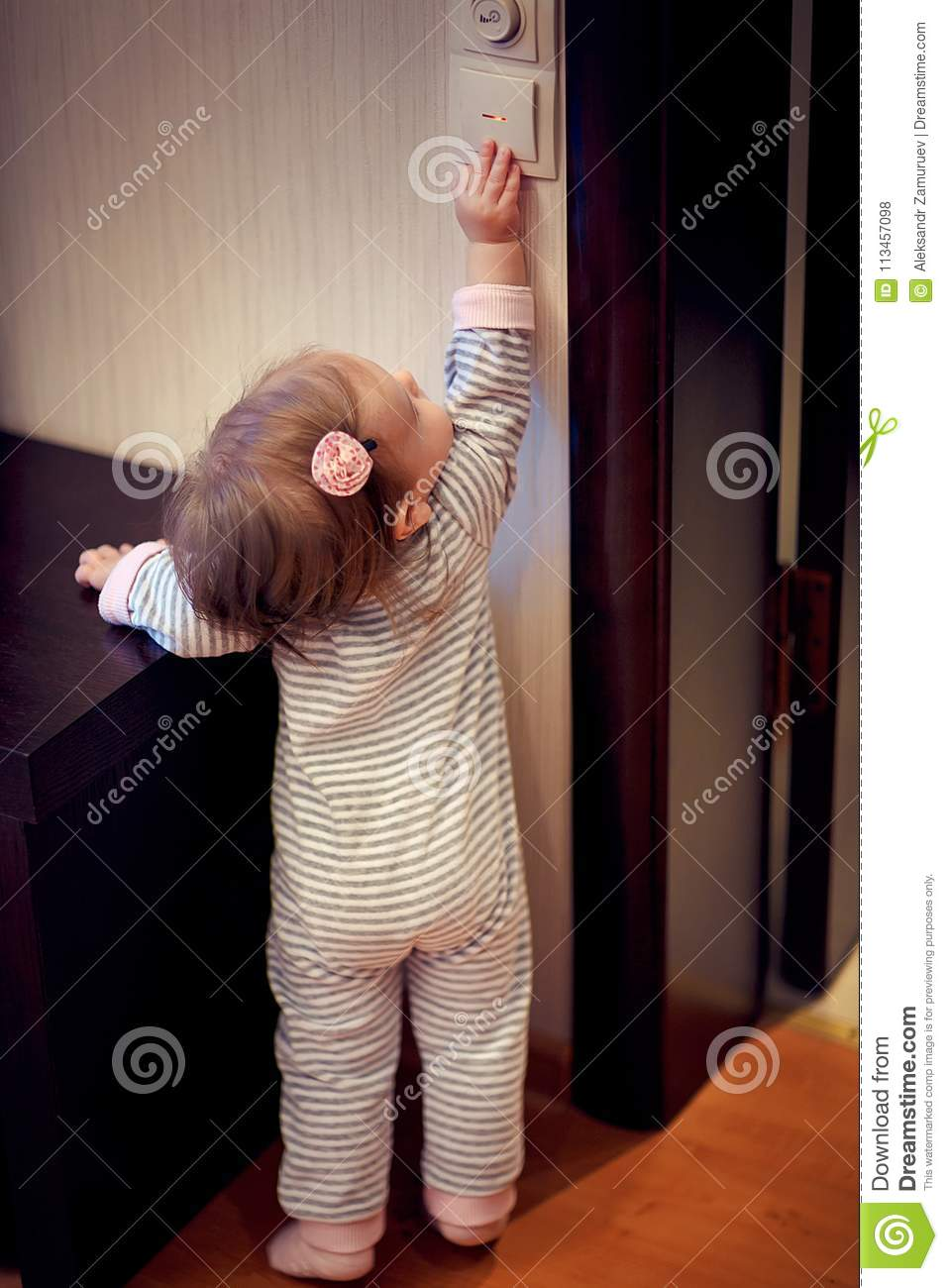 Young girl standing and touching switch