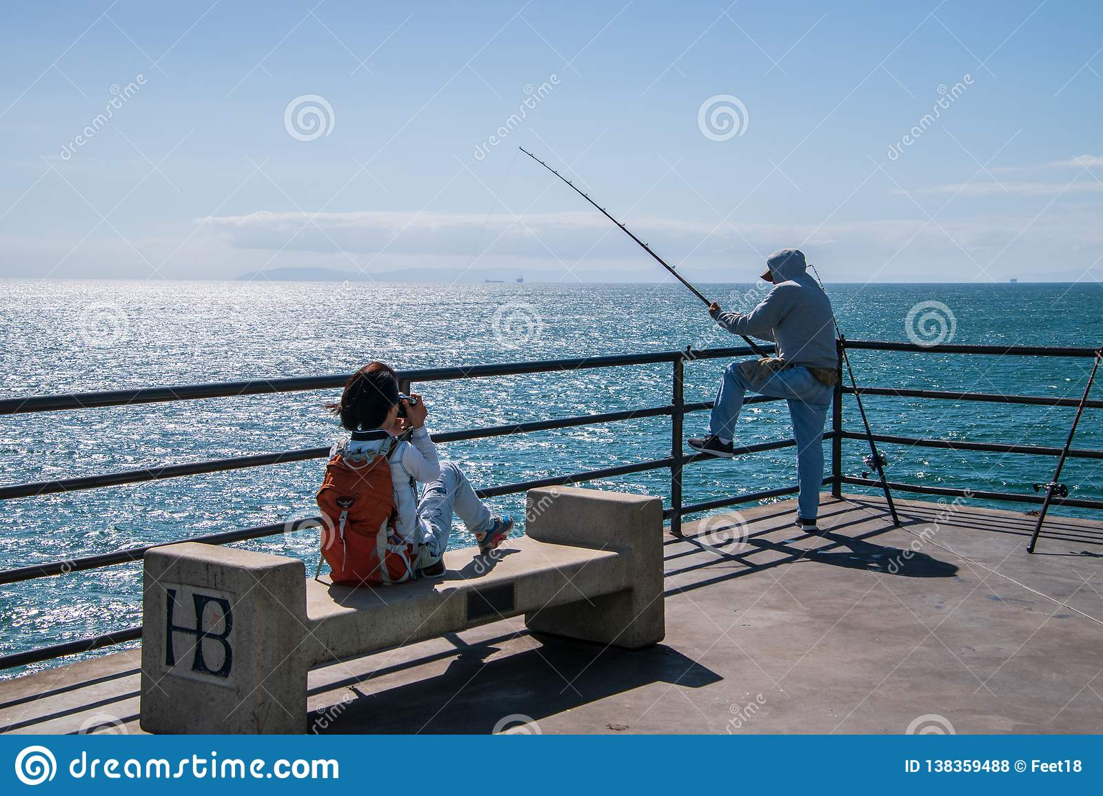 Young Girl Taking A Picture Of A Fisherman Fishing Off Of The End Of