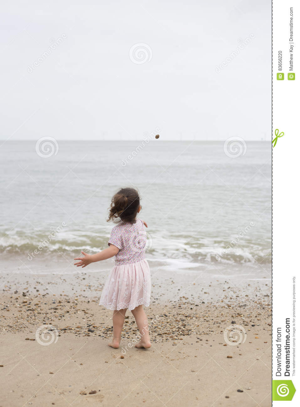 Young girl throwing a stone into the sea