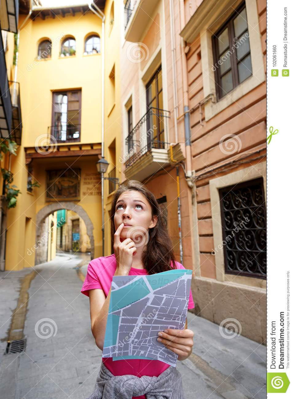 Young girl tourist with map searching for directions on the street.
