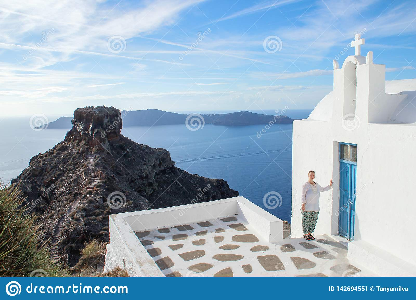A young girl tourist in white clothes is smiling next to a white church on the island of Santorini. Aegean Sea and Volcano on a su