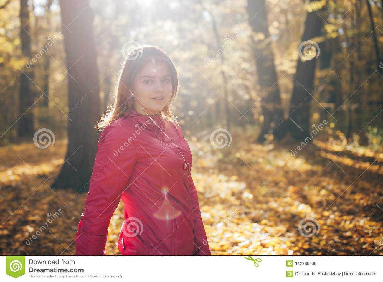 Young girl trains in the morning autumn park. Close up portrait