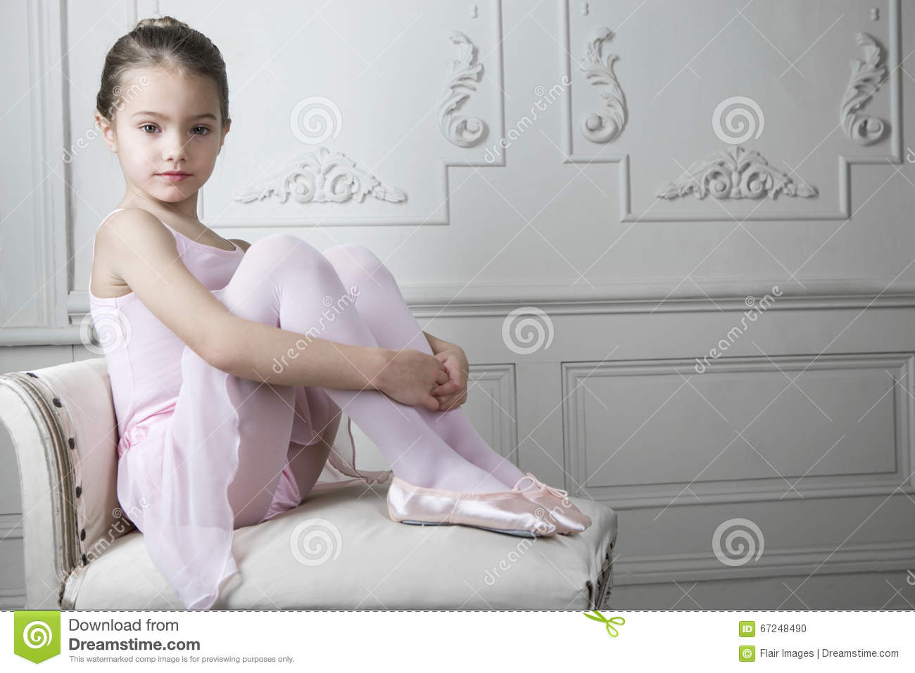 60a3b9b35bc255 Young Girl In A Tutu And Ballet Shoes Sitting On A Chair Stock Photo ...
