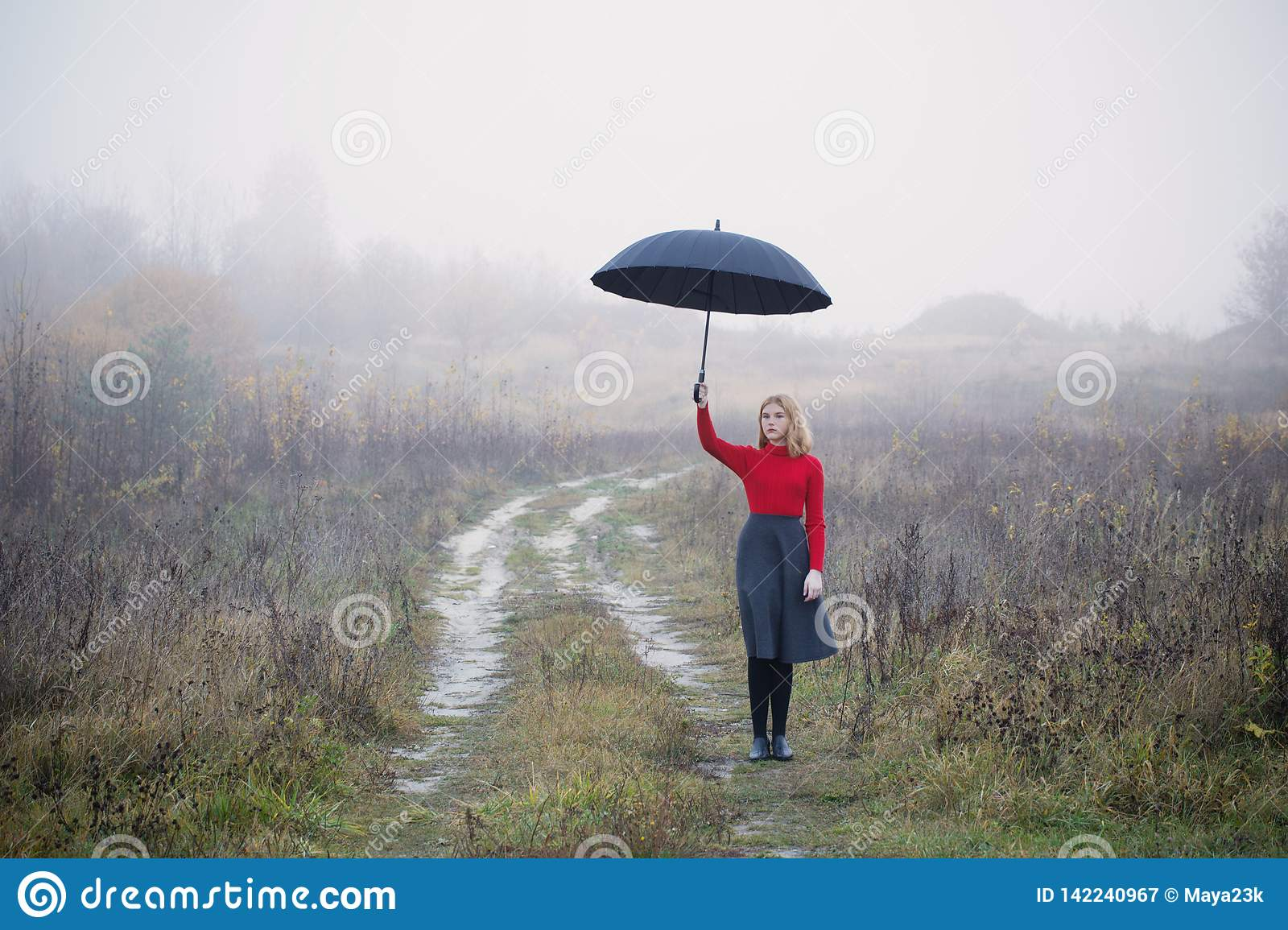 girl with umbrella in autumn field