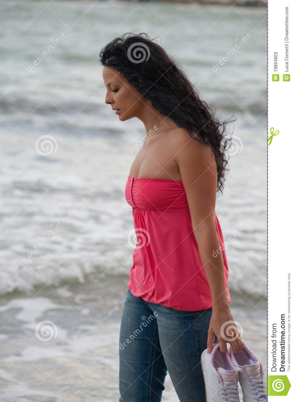 young brunette european girl walking in the water.