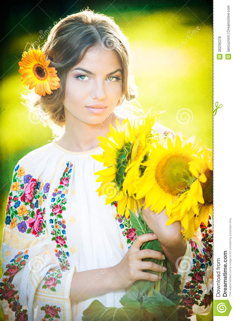 c773115514 Young girl wearing Romanian traditional blouse holding sunflowers outdoor  shot. Portrait of beautiful blonde girl with bright yellow flowers bouquet.