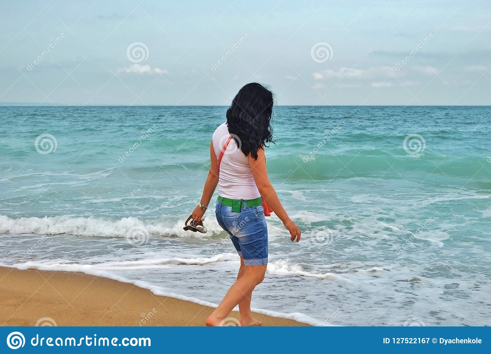A young girl in a white Tshirt is walking along the sand in the sea. brunette on the shore of the azure sea in Bulgaria