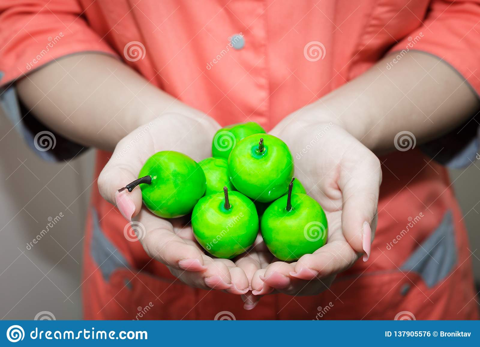 The young girls hand holding a small green Apple. Nutritionist recommends apples