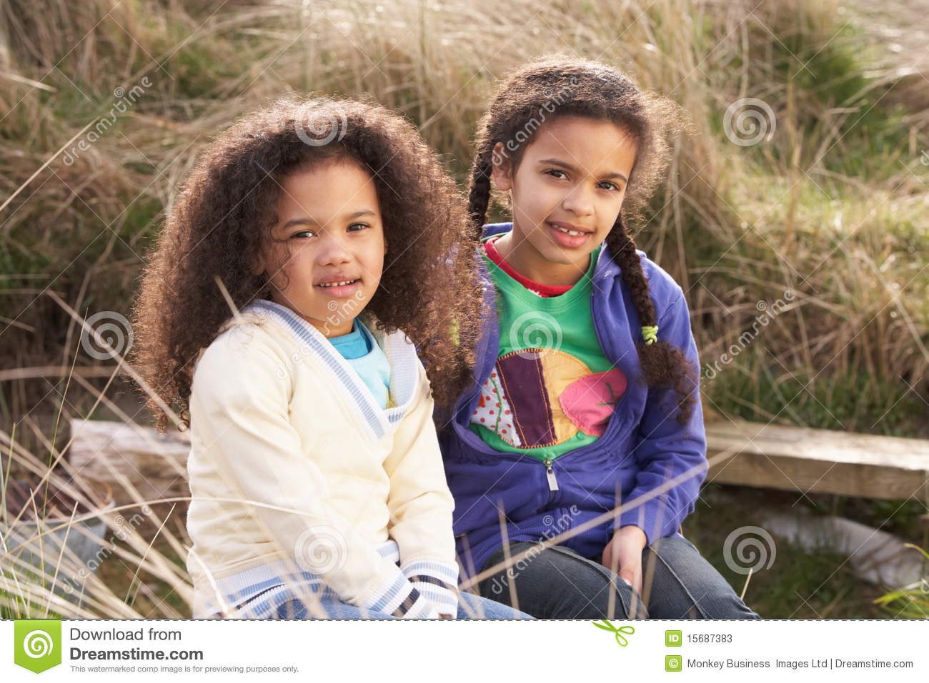 Young Girls Playing In Field Together