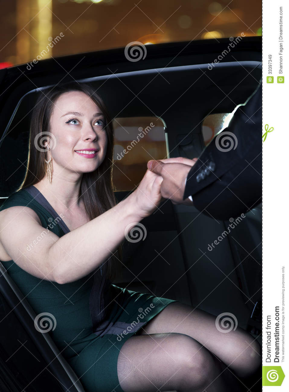 Young Glamorous Woman Being Helped Out Of Her Car At A