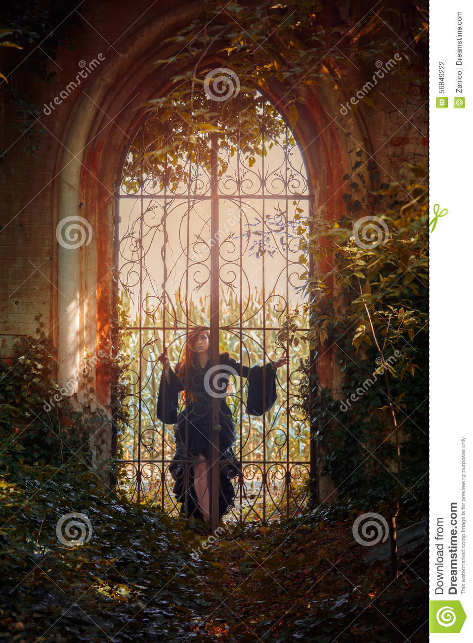 Young goth girl pose behind a gate