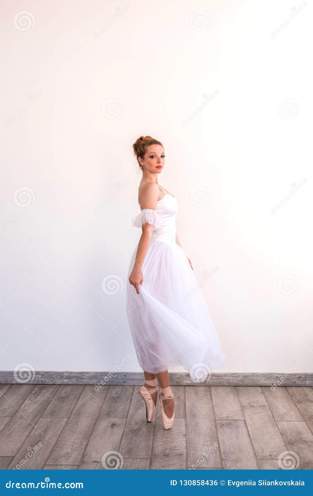 Young graceful ballerina dancing on white studio.