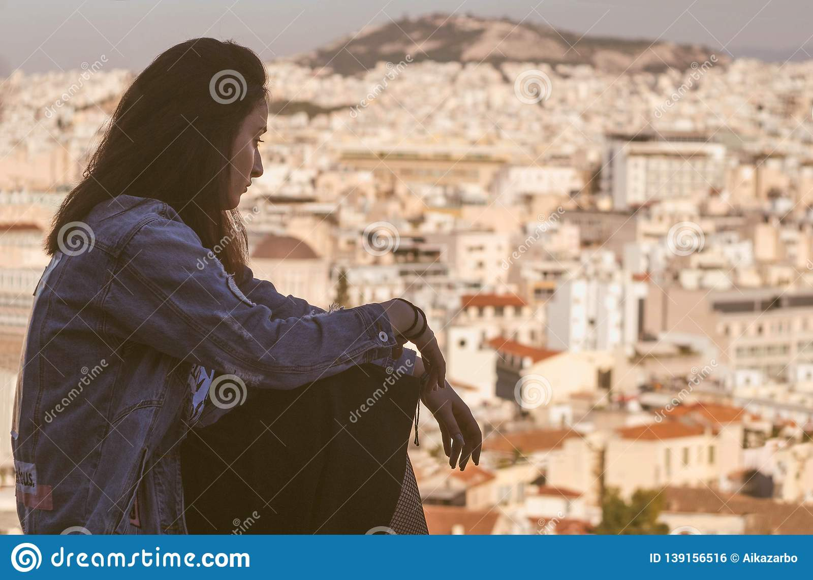 Young Greek girl on the background of the panorama of the city in the tourist area of Athens Anafiotika in Greece