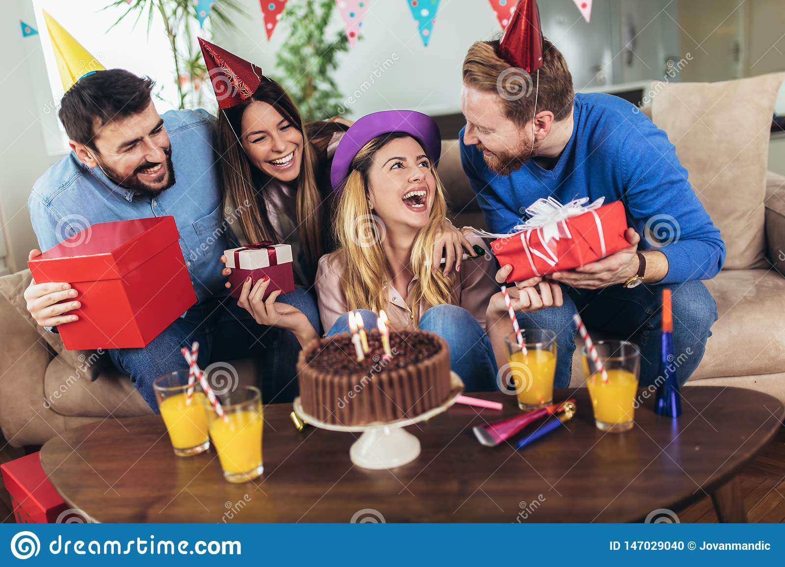 Group of happy friends celebrating birthday at home and having fun