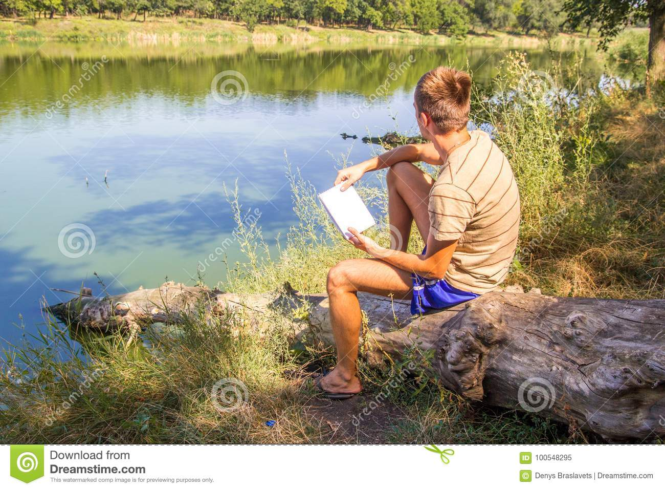 A Young Guy, With A Notebook On The Banks Of The River, Lake