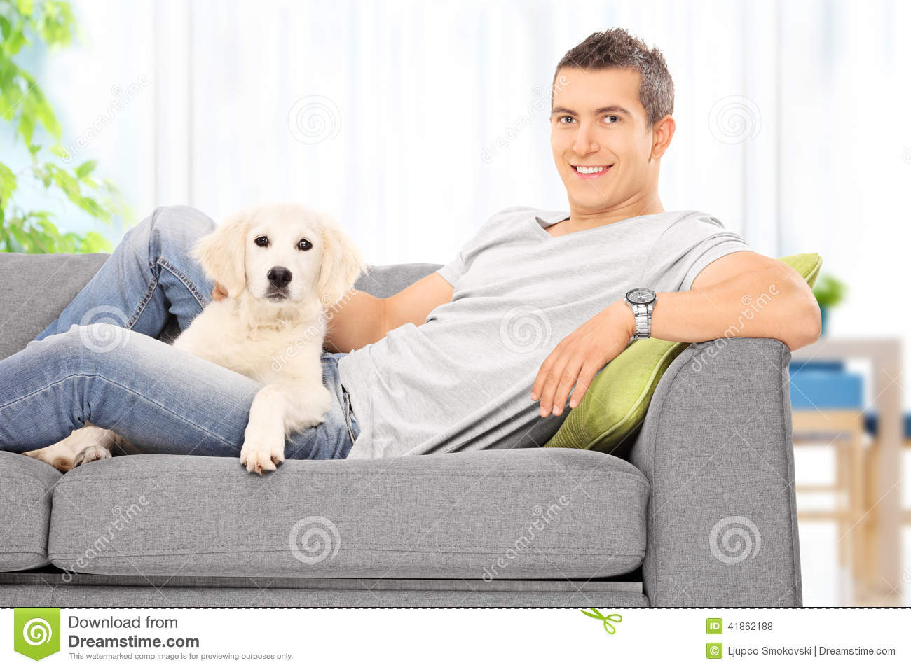 Young Guy Sitting On Couch With A Puppy At Home Stock Photo ...