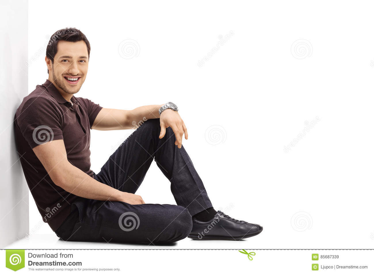 Young Guy Sitting On The Floor And Leaning Against A Wall