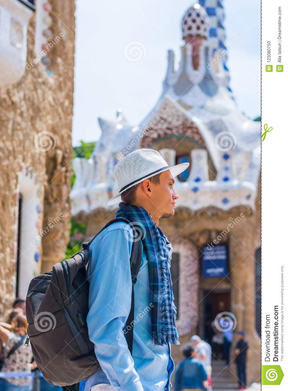 A young guy stands in a white hat and scarf with backpack near a  gingerbread house in Guell Park d3ffcf94182c