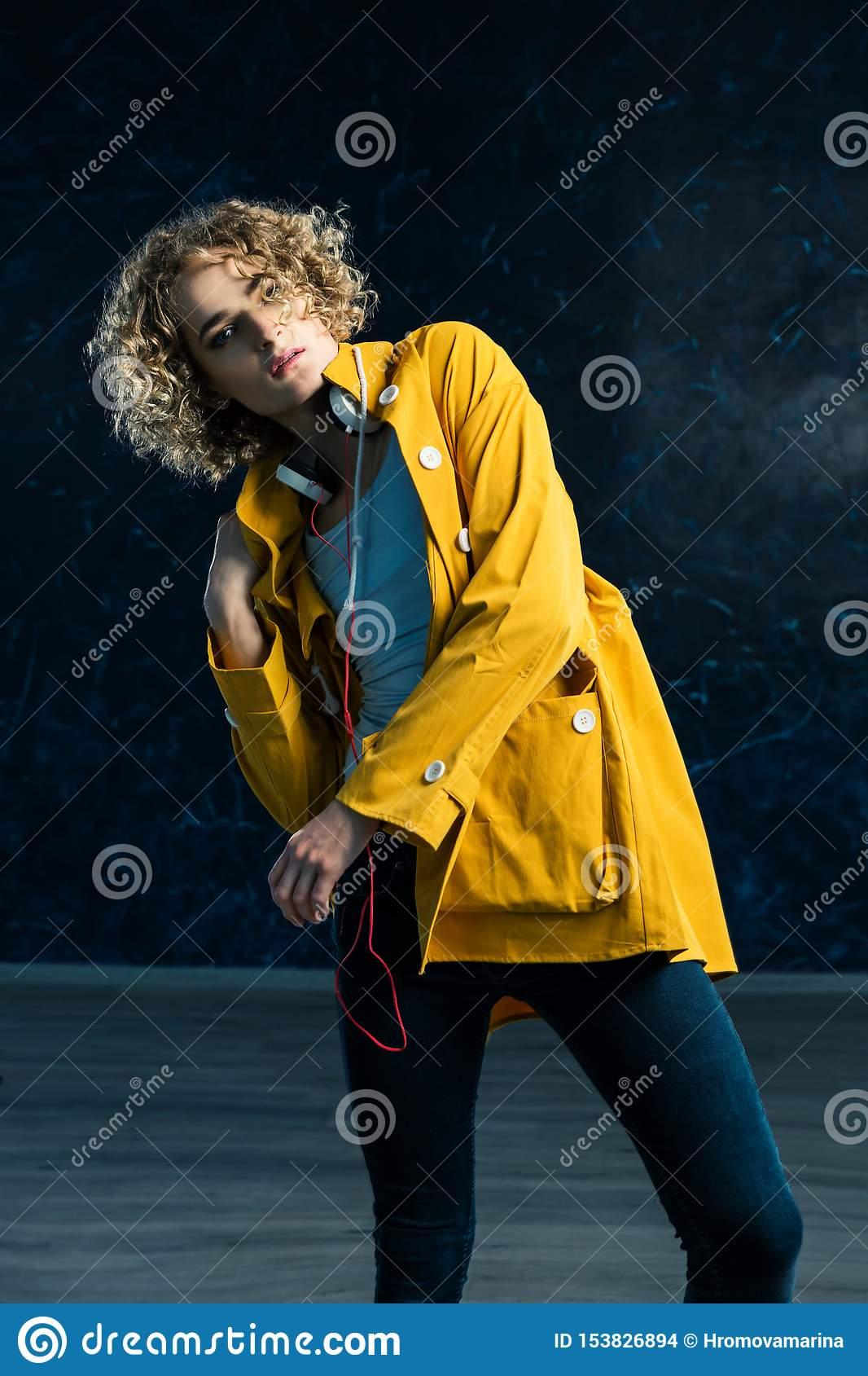 A young guy with a surfer`s hair in a yellow jacket and headphones is dancing against