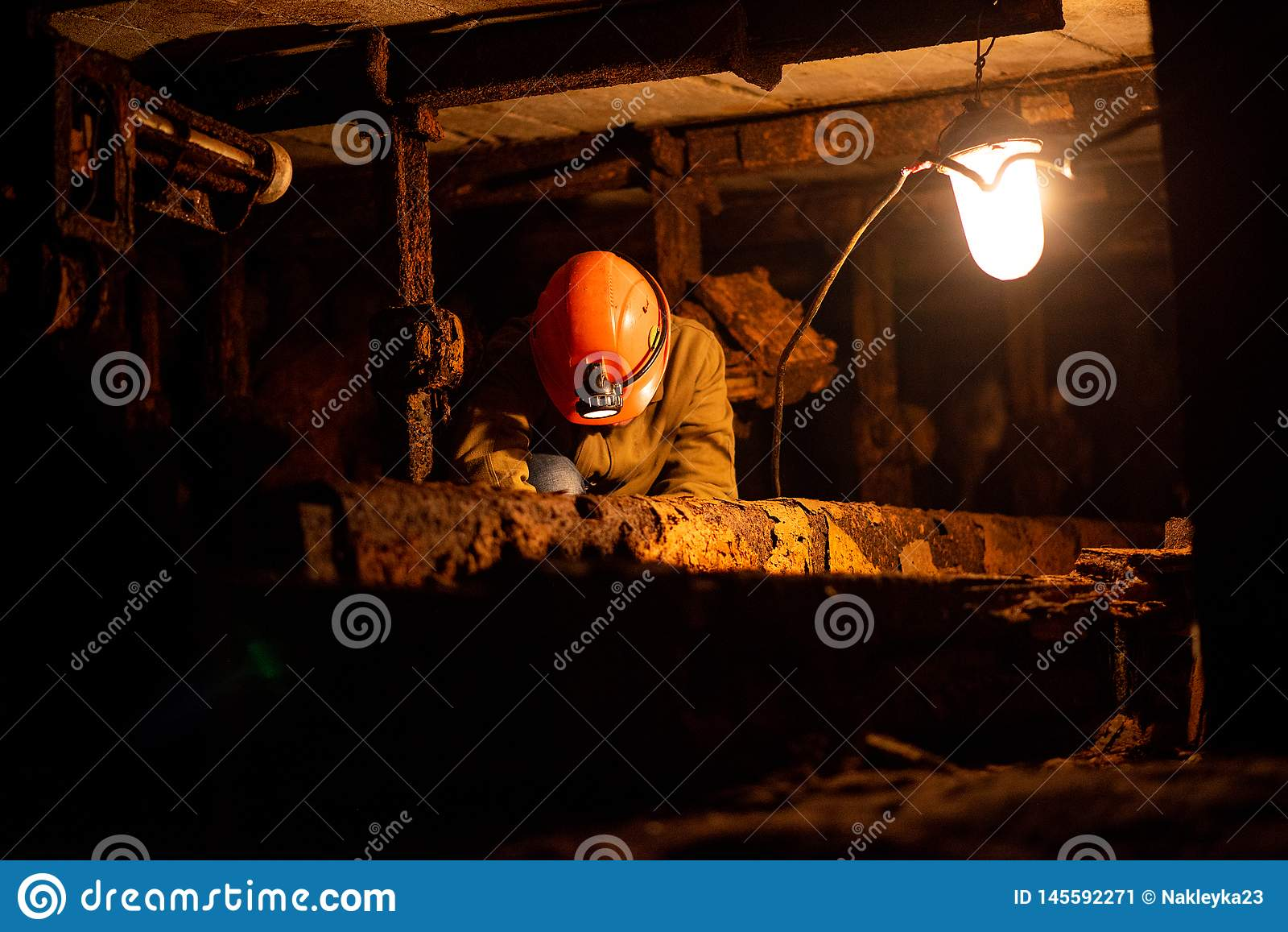 Young guy in a working uniform and protective helmets, sitting in a low tunnel