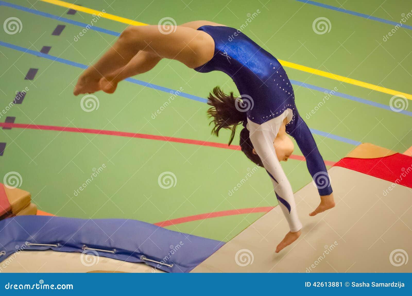 Download Young Gymnast Girl Performing Jump Back Handspring Stock Image
