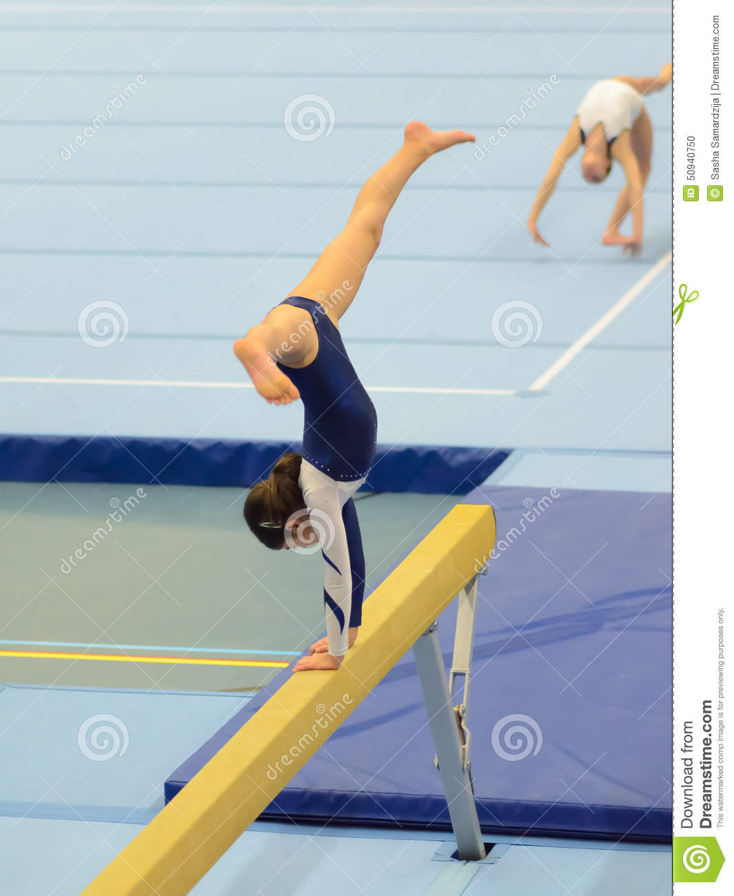 Young Gymnast Girl Performing Routine On Balance Beam