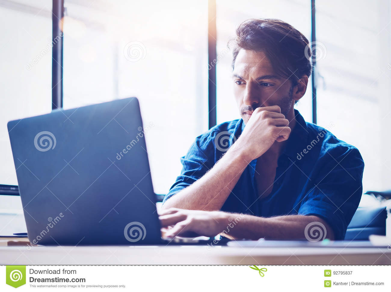 Young handsome banking finance analyst working at sunny office on laptop while sitting at wooden table.Businessman