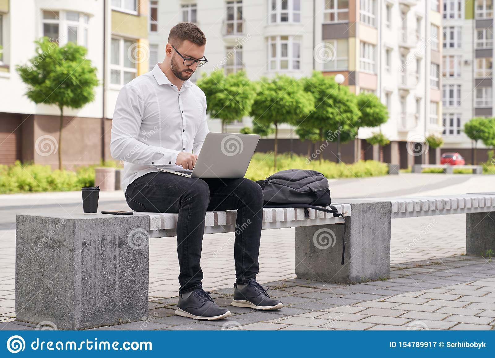 Handsome man sitting on bench, working on laptop outdoors.