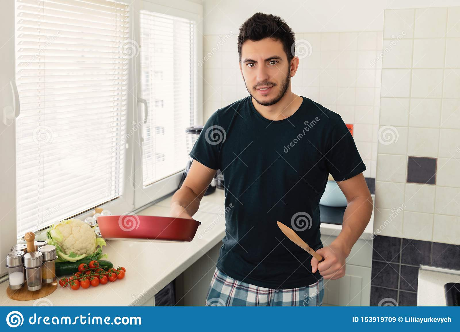 A young handsome brunette man is standing in the kitchen and holding a frying pan in his hands.