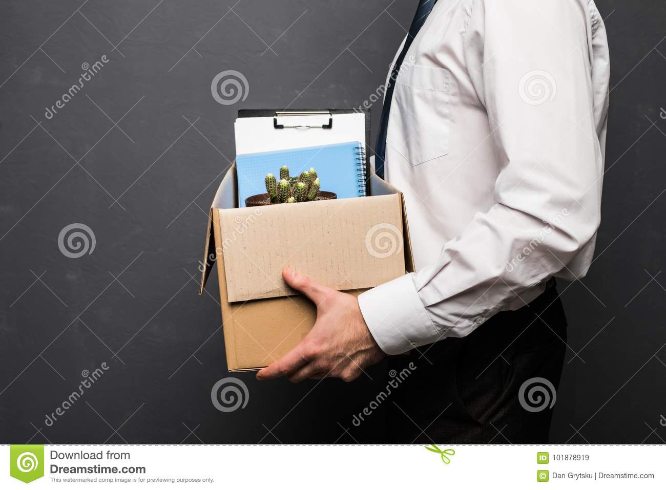 Young handsome businessman in light modern office with carton box