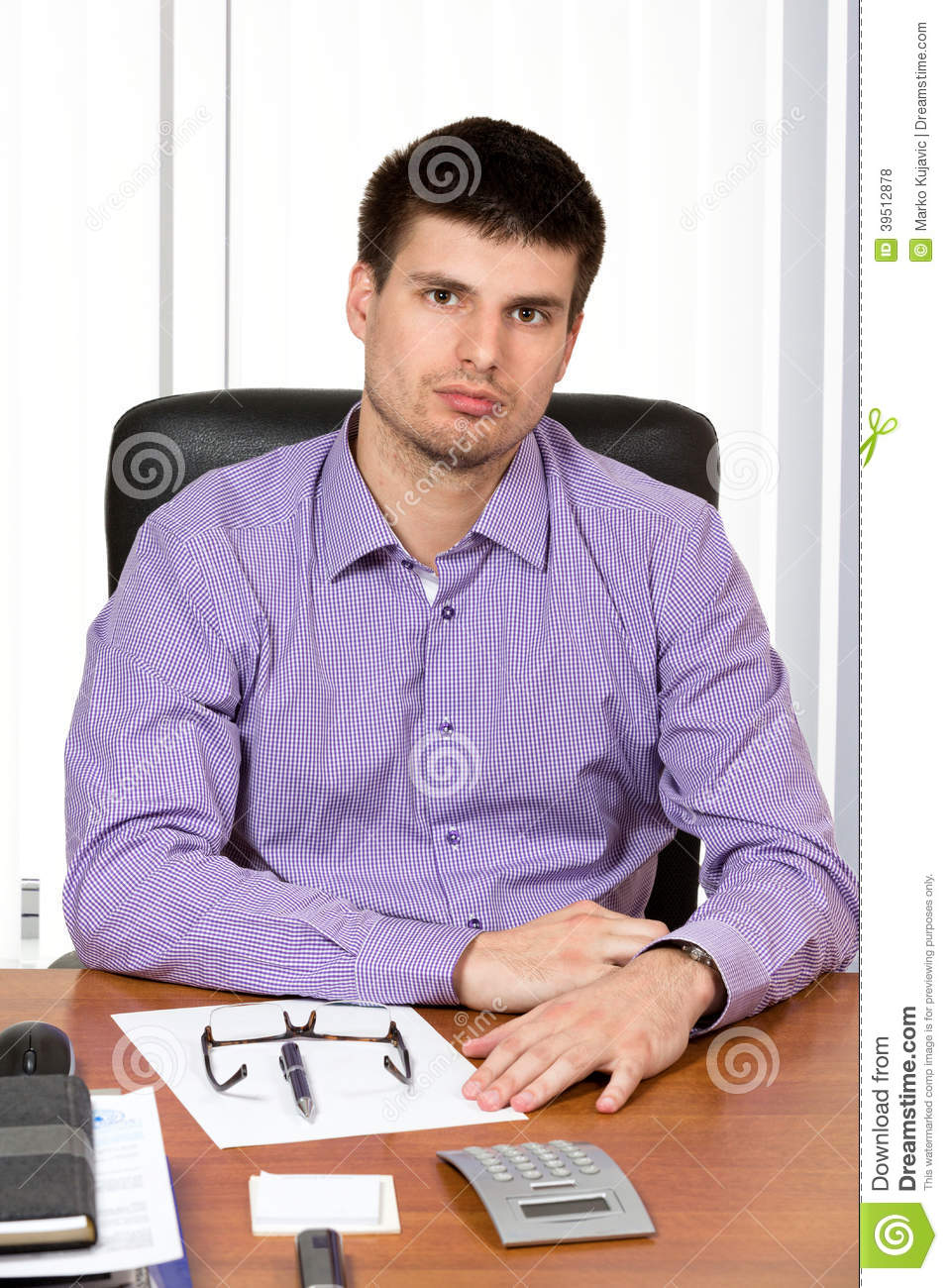 Young handsome businessman sitting at his desk