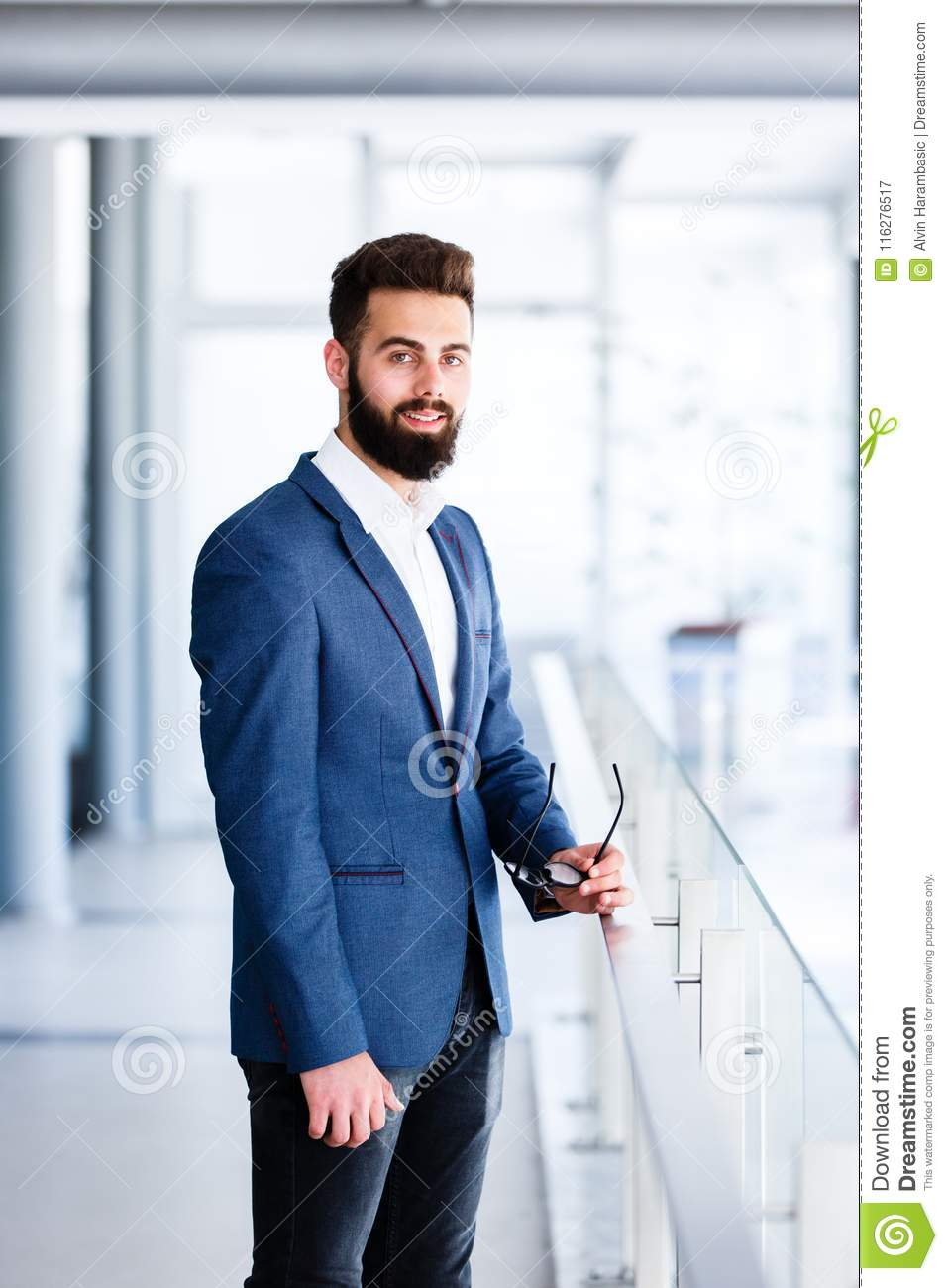 Young Handsome Businessman Standing At Company`s Indoor