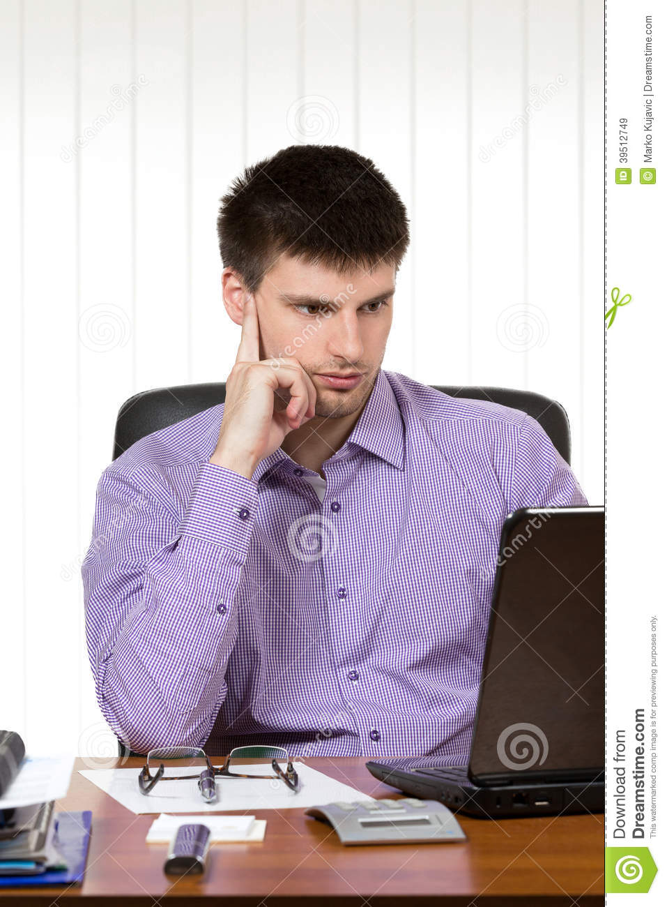 Young handsome businessman working on laptop