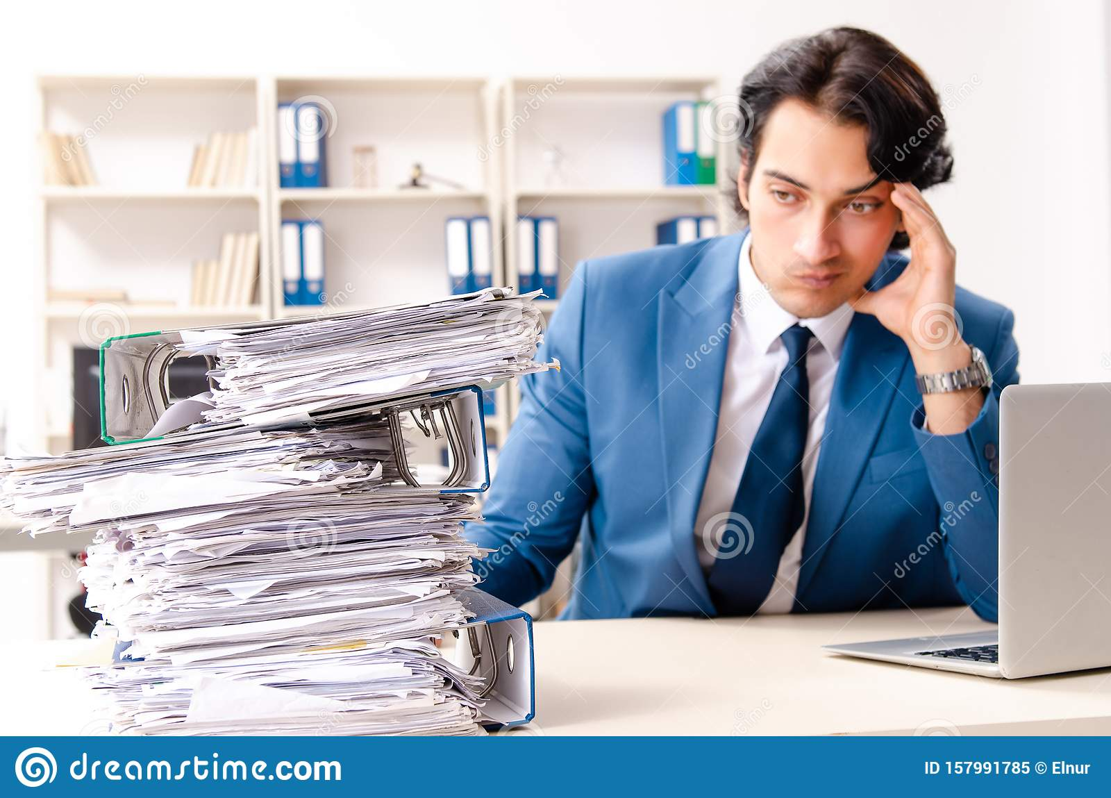 Young handsome busy employee sitting in office
