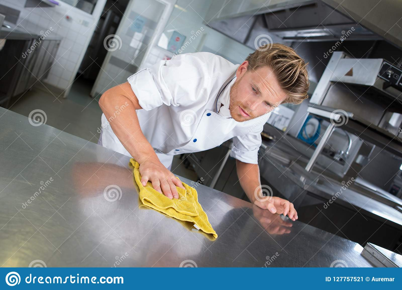 Young handsome male cook cleaning restaurant kitchen